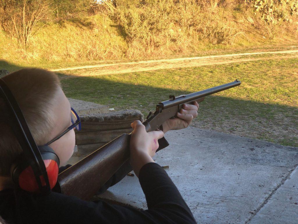 Our younger son aiming his rifle.